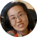 Alice with shoulder length black hair and thin eyeglasses, is wearing colorful flower patterned top and smiling directly at the camera.