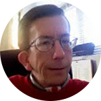 Andrew with short brown hair and eyeglasses, in red sweater, is smiling at the camera.