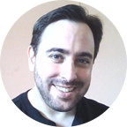 Gregg with dark short hair and beard, wearing black shirt, is smiling directly at the camera.