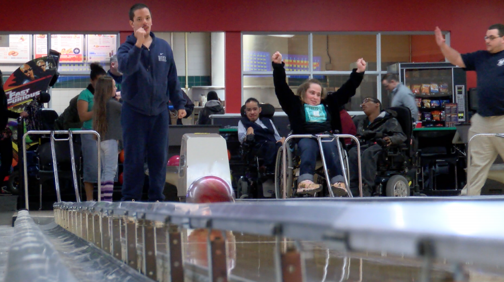 Group of people going bowling. Man on left is watching beyond the camera. Woman in wheelchair on right is raising her arms as if her bowling ball hit the pins.