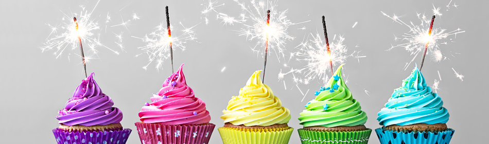 a row of colorful cupcakes with sparkling candles