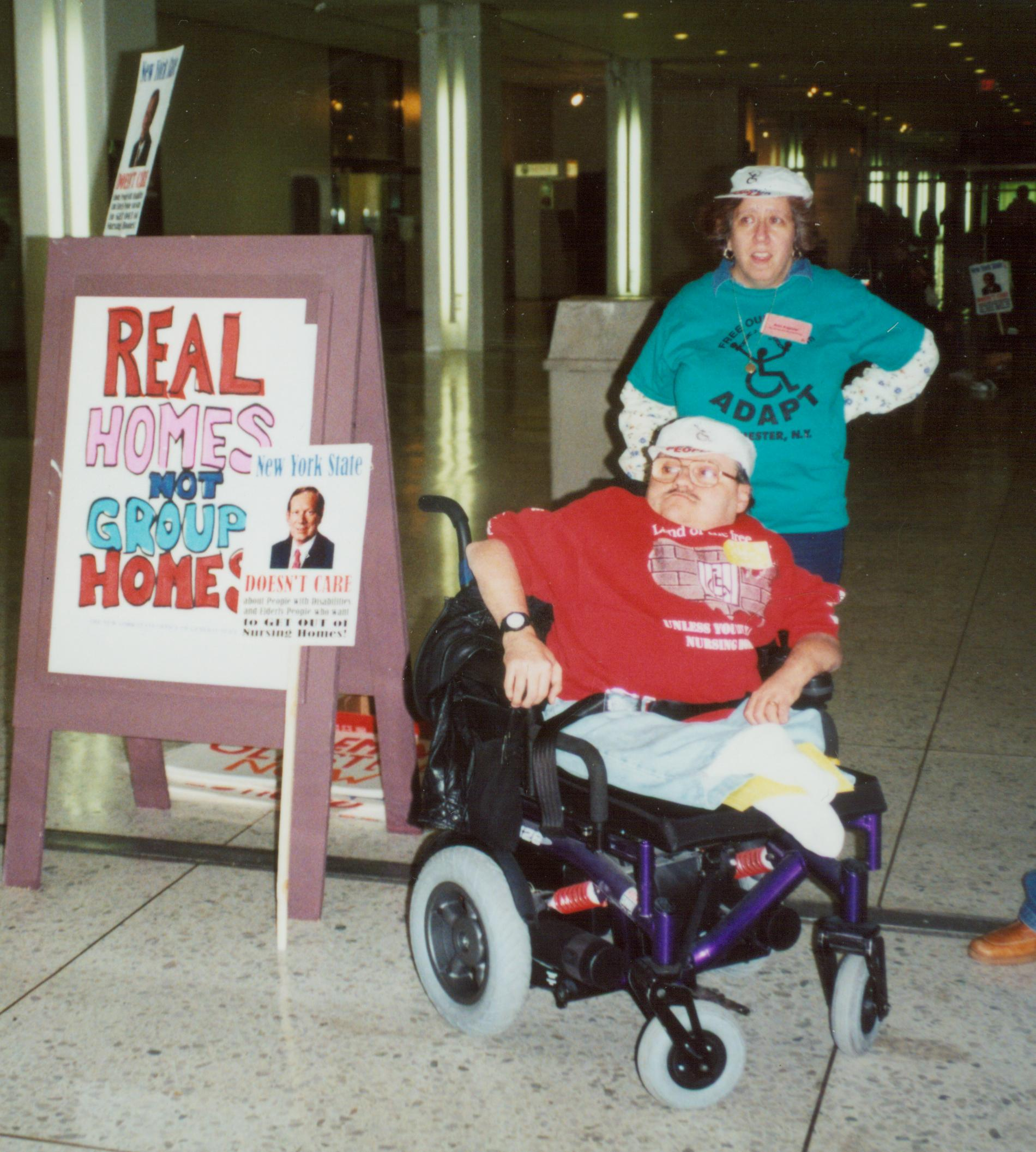"""Picture of Joe Bonomo in his wheelchair next to a sign that reads 'Real Homes not Group Homes"""""""